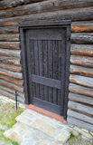 Detail of log cabin outer wall with closed wood door Royalty Free Stock Image