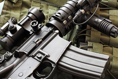 Detail of M4A1 (AR-15) carbine and tactical vest. Detail of a scratched M4A1 (AR-15) carbine and green military tactical vest Stock Image