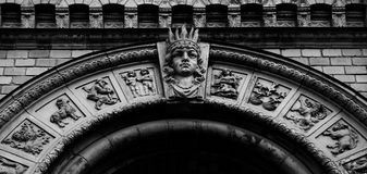 Detail on the main arch with the zodiac symbols. Shot in black and white detail of the sculpture on the facade of this historic building representing some stock photography