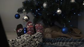 Detail of male and female feet wearing warm winter socks, placed on the floor with nicely decorated Christmas tree and. Christmas toys in the background. Having stock video footage