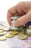 Detail of male hand checking money with stethoscope Stock Photos