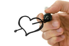 Male hand drawing heart shape pierced with arrow Royalty Free Stock Images