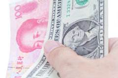 Detail of male hand holding US dollar and Chinese RMB banknotes. On white background, business and finance concept Stock Photos