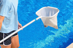 Detail on a man cleaning the swimming pool with a net Stock Photos