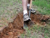 A detail of a man digging