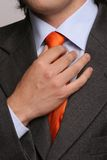 Detail of a man, fixing his tie. Isolated in soft light royalty free stock photo