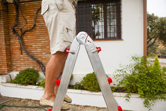 Detail of man legs in a ladder. Stock Photos