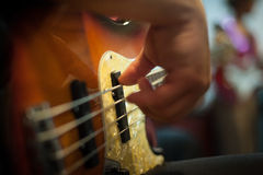 Detail of man playing bass instrument. Human hands while playing electric bass instrument in selective focus Royalty Free Stock Photography