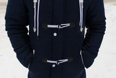 Detail of a man`s torso in a fashionable winter jacket. Blue parka with laces and rivets. Royalty Free Stock Photography