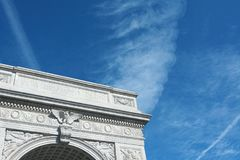 Marble arch in Washington Square Park. Detail of the marble arch in Washington Square Park, against a blue sky with light clouds Royalty Free Stock Image