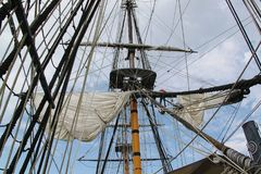 Detail of mast of ship. Detailed rigging with sails. Vintage sailing ship block and tackle. stock photos