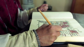 Detail of medieval scholar who writes in calligraphic writing stock video footage