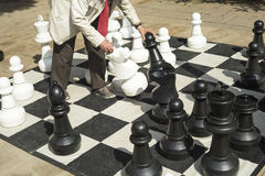 Detail of men playing gigantic chess outdoors on a sunny day. Stock Photo