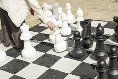 Detail of men playing gigantic chess outdoors on a sunny day. Stock Images