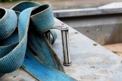 Detail of metal buckle on a blue ratchet strap. Detail of metal buckle on a blue strong industrial load strap, on a metal trailer royalty free stock photo