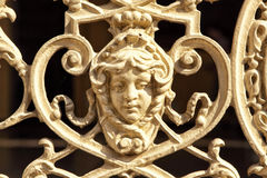Detail of metal historic railing with girl face Stock Image