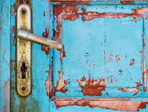 Detail of metal knob on old rusty textured wooden door Stock Image