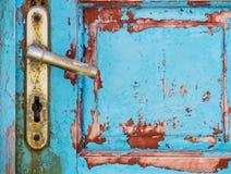 Detail of metal knob on old rusty textured wooden door Stock Image