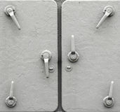 Detail of metal ship doors. Gray color background of an old ship metal doors with a number of handles Stock Images