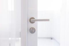 Detail of a metallic knob on white door Royalty Free Stock Photos