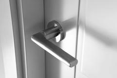 Knob on door. Detail of a metallic knob on white door horizontal royalty free stock photos