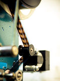 Detail of 35mm movie projector in theater. With film rolling on spool stock photo