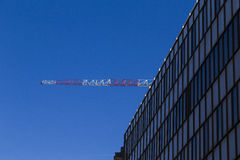 Detail of a Modern Building with Construction Crane in the Backg Royalty Free Stock Photo