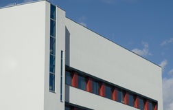 Detail of a modern building. White plastered building with red window frames Stock Photos