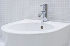 Detail of a modern ceramic hand wash basin. With chrome water mixer tap and mosaic wall Stock Image