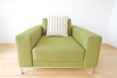Detail of a modern green armchair. Isolated on white backround and laminated floor Stock Photos