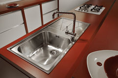 Detail of modern kitchen in red. Detail of a red modern kitchen, kitchen cabinets, gas stove and sink stock photos
