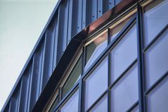 Detail of a modern steel clad building with a window to match the roof pitch. Blue steel siding and sheet metal flashing over a divided light matching peaked Royalty Free Stock Photos