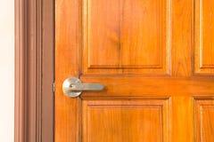 Detail of Modern style metallic door handle on wooden door. stock photography