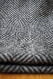 Detail of a modern woolen purse with black & white lines in the shape of arrows (fish bone pattern). Detail of a modern woolen purse with black and white lines Royalty Free Stock Image