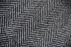 Detail of a modern woolen purse with black & white lines in the shape of arrows (fish bone pattern). Detail of a modern woolen purse with black and white lines Royalty Free Stock Photo