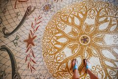 Detail of mosaic pattern floor, ocean theme, Oceanographic Museum of Monaco, historic building. Woman feet wearing sandals, summer mood stock image