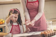 Girl sprinkling flour on the kitchen counter stock photos