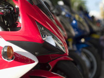 Detail of motorbike. Front detail of heavy motorbike. Long row of blurred motorbikes in the background Stock Images