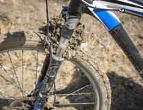 Detail of a mountain bicycle front wheel dirty with mud. A detail of a mountain bicycle front wheel dirty with mud Royalty Free Stock Images