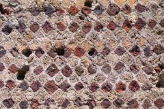 Detail of multi-coloured brickwork at excavated site at Pompeii, Italy. Showing diamond shaped layout and mortar joints royalty free stock photography