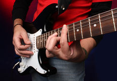 Detail of a musician playing a black electric guit Royalty Free Stock Photo