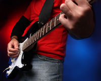 Detail of a musician playing a black electric guit Royalty Free Stock Photos