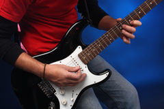 Detail of a musician playing a black electric guit Royalty Free Stock Image
