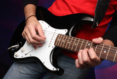Detail of a musician playing a black electric guit Stock Image