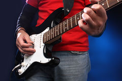 Detail of a musician playing a black electric guit Royalty Free Stock Images