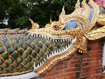Detail of Naga golden dragon head with big white teeth. Ornamental buddhist pattern in buddhist temple in North Thailand Royalty Free Stock Photo