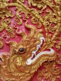 Detail of Naga golden dragon head with big white teeth. Ornamental buddhist pattern in buddhist temple in North Thailand Royalty Free Stock Image