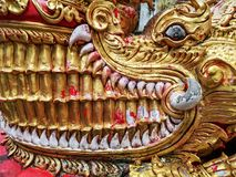 Detail of Naga golden dragon head with big white teeth. Ornamental buddhist pattern in buddhist temple in North Thailand Royalty Free Stock Photos