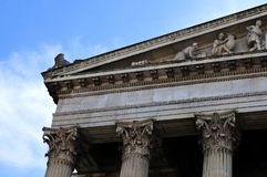 Detail of a neoclassical gable. Detail of a gable at historic building in neoclassical style with corinthian columns and lion sitting on roof stock photo