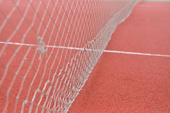 Detail of net tennis on field made from red granule rubbe. Selec Royalty Free Stock Photography
